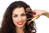 Beautiful smiling woman with make-up brushes near her face
