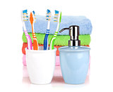 Four colorful toothbrushes, liquid soap and towels
