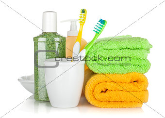 Toothbrushes, cosmetics bottles and two towels