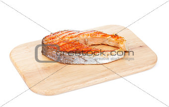 Grilled salmon steak on cutting board