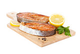 Grilled salmon with lemon and herbs on cutting board