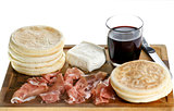 cutting board with small round flat bread, ham, cheese and glass of red wine, typical dish of Emilia-Romagna