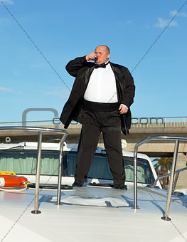 Fat man in tuxedo with glass wine