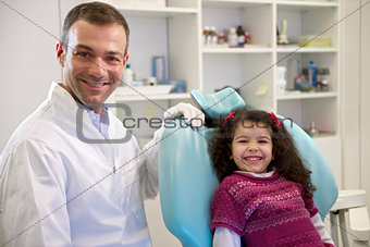 Portrait of child and dentist in dental studio, looking at camer