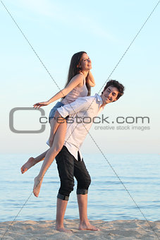 Couple playing piggyback on the beach