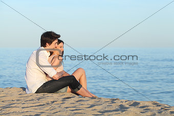 Couple cuddling sitting on the sand of the beach