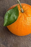 ripe round orange with stem and leaf on wooden table