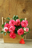 flowers roses in a vase on wooden background