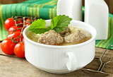 Soup with meatballs and vegetables in white bowl