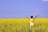 happy teenager standing in an oilseed rape field