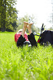 Happy tourist enjoying relaxation lying barefoot in green grass