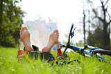Cyclist reads a map lying barefoot on green grass outdoors in summer park
