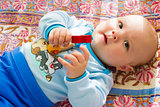 adorable baby with a toy in the hand on a colored blanket