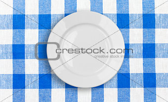 white plate on blue checked fabric tablecloth
