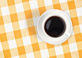 Top view of black coffee cup on checked tablecloth