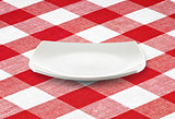 white square empty plate on red gingham tablecloth
