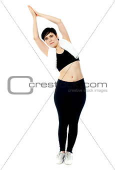 Fit female instructor doing stretching exercise