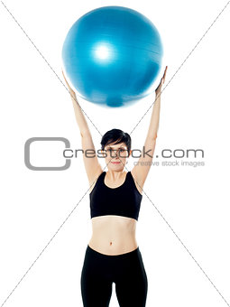 Beautiful woman holding pilates ball