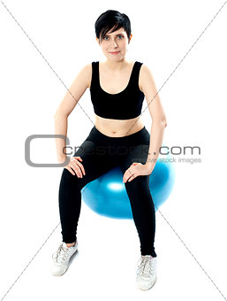 Fitness woman isolated sitting on pilate ball