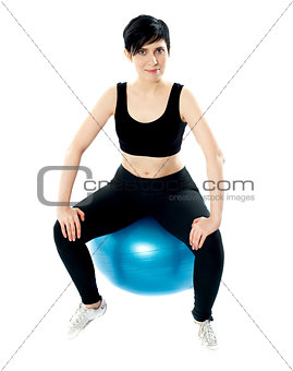 Young athlete sitting on a swiss ball