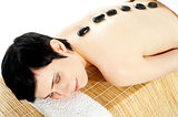 Woman getting spa treatment with hot stone