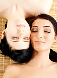Massage of two beautiful females in spa salon