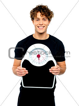 Attractive athlete showing weighing scale