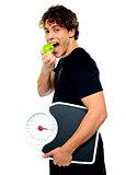 Smart boy eating green apple