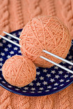 Two balls of pink yarn and knitting needles on a blue plate