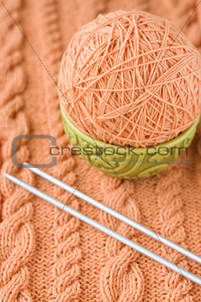 A peach-colored ball of yarn are in the national dish and needles for knitting