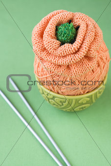 A ball of orange yarn to knit a flower on a green background