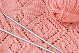 A fragment of a knitted blankets, pink skein of yarn and knitting needles