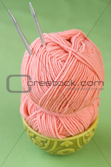 Large pink skein of thread in a plate with oriental ornament national and knitting needles on a green background