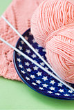A ball of pink yarn and knitting needles on a blue plate