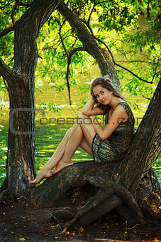 beautiful girl sitting on a large tree