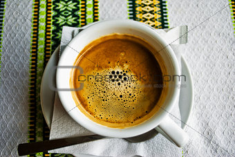 A cup of coffee on the embroidered tablecloth