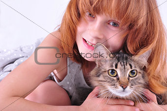 little girl hugging her cat