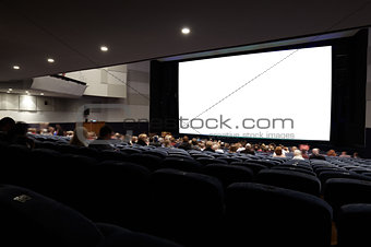 Cinema auditorium with people in chairs watching movie.