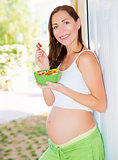 Expectant young lady eat salad