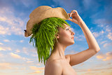 woman in profile with eco hair-style and hat