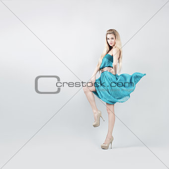 Woman in Turquoise Dress on Gray Backgound