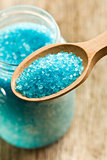 blue bath salt in wooden spoon