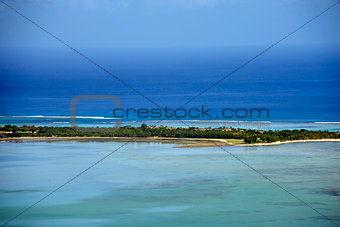 Small tropical desert island with turquoise waters and clear sky
