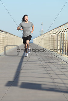 Front view of a sportsman running on a bridge