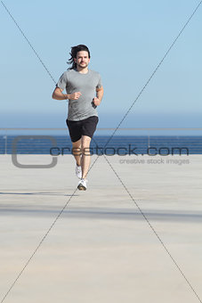 Front view of a sportsman running on the concrete of the seafront