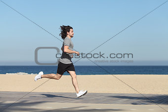 Side view of a man running on the seafront of the beach