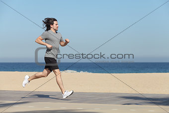 Sportsman running on the seafront of the beach