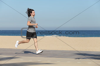 Man running on the seafront of the beach