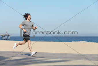Young sportsman running on the seafront of the beach