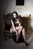 Elegant young girl sitting in an velvet chair